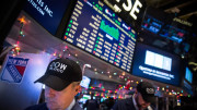 """NEW YORK, NY - DECEMBER 23:  Traders wear hats that say """"DOW 18,000"""" as they work on the floor of the New York Stock Exchange during the afternoon of  December 23, 2014 in New York City. The Dow Jones Industrial Average crossed a landmark by closing above 18,000 points today.  (Photo by Andrew Burton/Getty Images)"""
